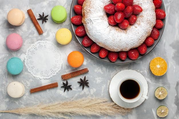 ホワイトにお茶とマカロンを添えたトップビューのおいしいストロベリーパイ