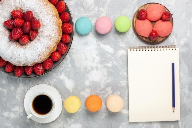Vista dall'alto deliziosa torta di fragole con tè su bianco chiaro