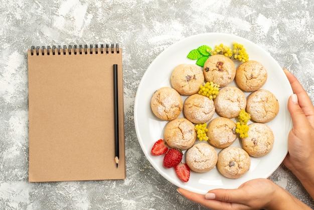ライトホワイトの背景にプレート内のおいしいシュガークッキーの上面図シュガークッキー甘いビスケットティーケーキ