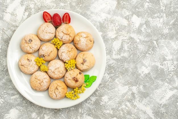 Вид сверху вкусного сахарного печенья внутри тарелки на белом фоне сахарное печенье сладкое печенье чайный торт