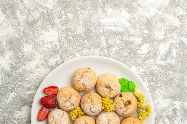 上面図白い背景の上のプレート内のおいしいシュガークッキーシュガークッキー甘いビスケットケーキティー