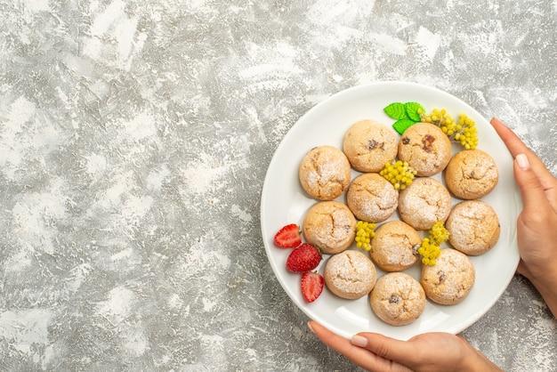 上面図白い背景の上のプレート内のおいしいシュガークッキーシュガークッキー甘いビスケットティーケーキ