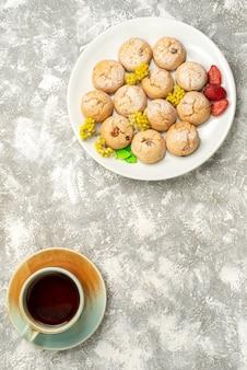 Вид сверху вкусное сахарное печенье с чашкой чая на белом фоне печенье, бисквит, сахарный торт, сладкий чай