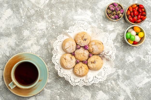 Vista dall'alto deliziosi biscotti di zucchero con la tazza di tè sulla superficie bianca biscotto zucchero biscotto dolce torta di tè