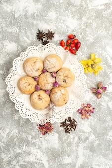Вид сверху вкусного сахарного печенья с сушеными цветами на белой поверхности сахарного бисквитного печенья, сладкого чая