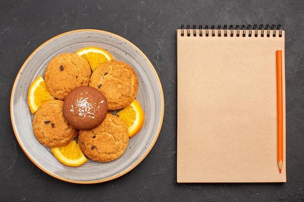 Вид сверху вкусное сахарное печенье со свежими нарезанными апельсинами на темном фоне сахарное печенье сладкое печенье фрукты