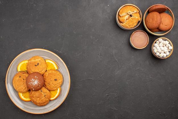 Вид сверху вкусного сахарного печенья со свежими нарезанными апельсинами на темном фоне, печенье, фруктовое сахарное печенье, сладкое