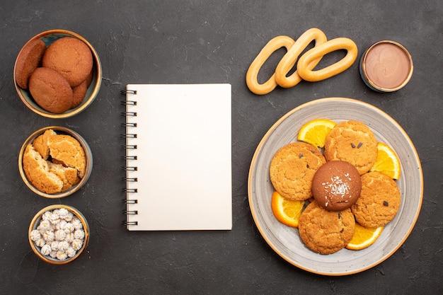 Вид сверху вкусное сахарное печенье со свежими нарезанными апельсинами на темном фоне печенье бисквитный сахарный торт десерт сладкий