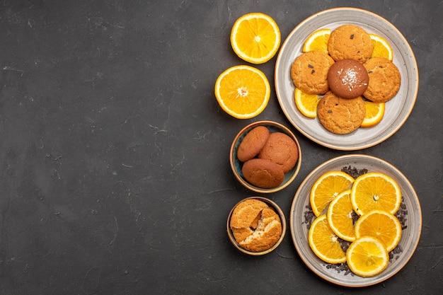 トップビュー暗い背景に新鮮なスライスしたオレンジとおいしいシュガークッキーシュガービスケット甘いクッキーフルーツケーキ