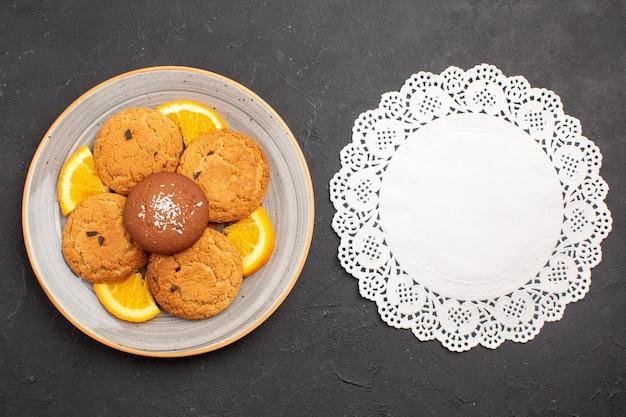 暗い背景に新鮮なスライスしたオレンジとシュガービスケットの甘いクッキーフルーツの上面図おいしいシュガークッキー