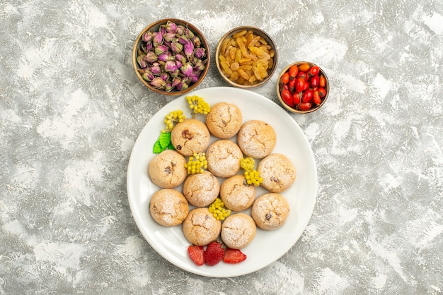 上面図白い背景にレーズンとおいしいシュガークッキークッキービスケットシュガーケーキスウィートティー