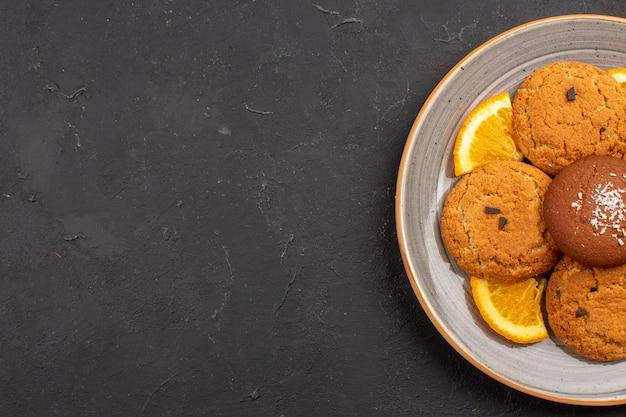 暗い背景のプレートの内側にスライスされたオレンジとシュガーフルーツビスケットの甘いクッキーの上面図