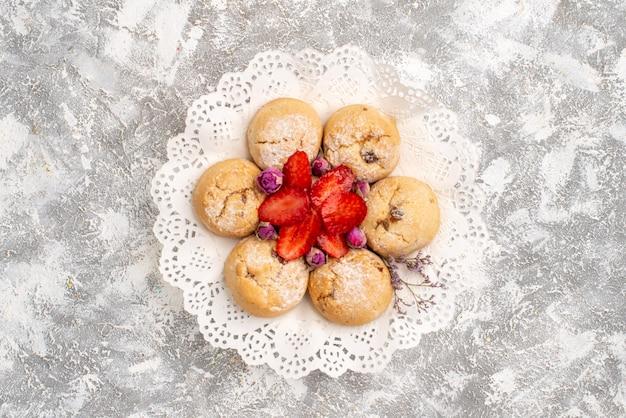 Vista dall'alto di deliziosi biscotti di zucchero con fragole sulla superficie bianca