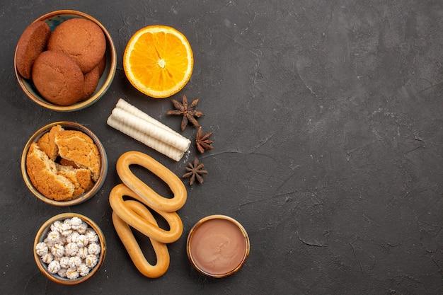 Вид сверху вкусное сахарное печенье со сладкими крекерами на темном фоне печенье, бисквит, сахарный торт, десерт, сладкое