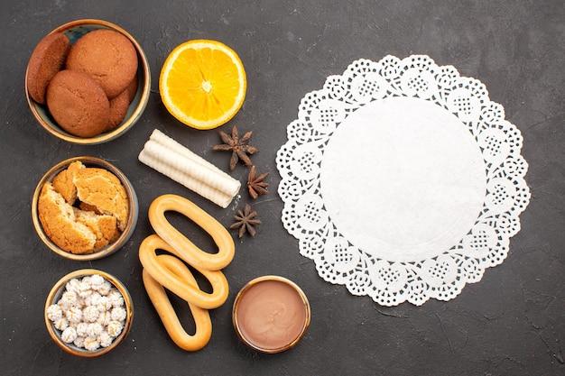 トップビュー暗い背景のクッキーに甘いクラッカーとおいしいシュガークッキービスケットシュガーケーキデザート甘い