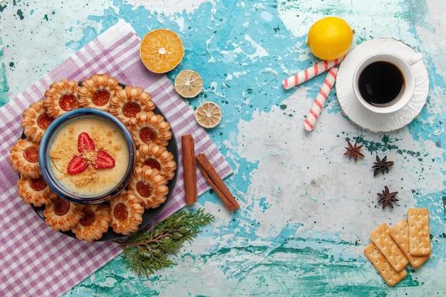 Vista dall'alto delizioso zucchero con tazza di caffè e dessert alla fragola su superficie blu