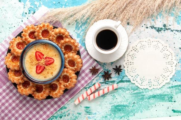 上面図水色の表面に一杯のコーヒーとイチゴのデザートとおいしい砂糖