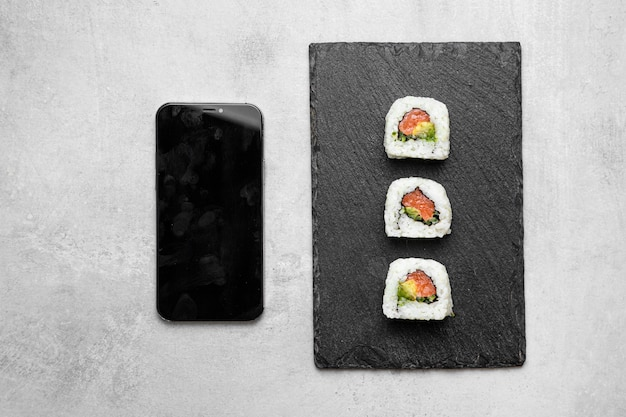 Top view delicious sushi and smartphone