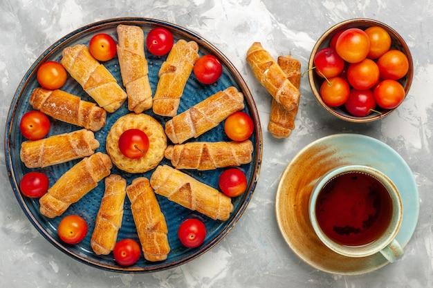 Vista dall'alto deliziosi bagel dolci con prugne acide e tè sulla scrivania bianco chiaro