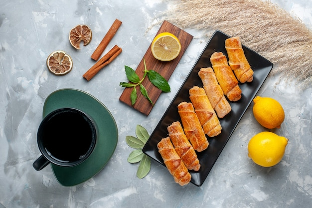 Вид сверху вкусные сладкие браслеты с лимоном, корицей и чаем на светлом столе, выпечка из сладкого сахара