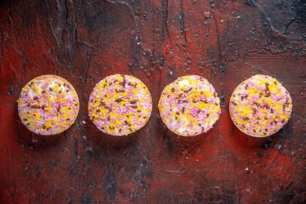 Вид сверху вкусное сладкое печенье на темно-красном фоне сладкий горизонтальный торт пирог бисквит сахарный чай