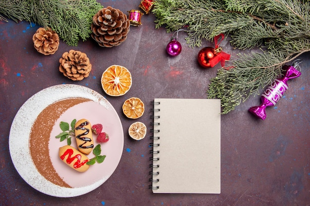 어두운 배경 쿠키 달콤한 비스킷 설탕 색 케이크에 크리스마스 장난감과 나무와 상위 뷰 맛있는 달콤한 비스킷
