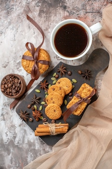 Top view delicious sweet biscuits with coffee seeds and cup of coffee on a light background sugar tea cookie sweet cocoa cake color
