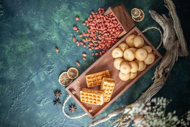 暗い表面にピーナッツと小さなケーキが付いたトップビューのおいしい甘いビスケット