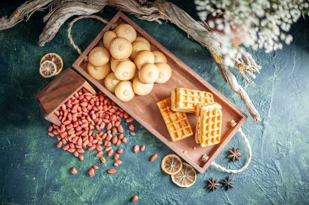 Vista dall'alto deliziosi biscotti dolci con arachidi e piccole torte su superficie scura
