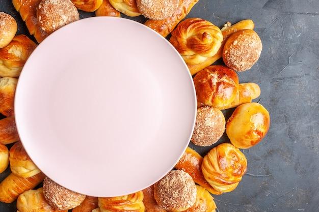 Вид сверху вкусные сладкие булочки с пустой тарелкой на темном фоне