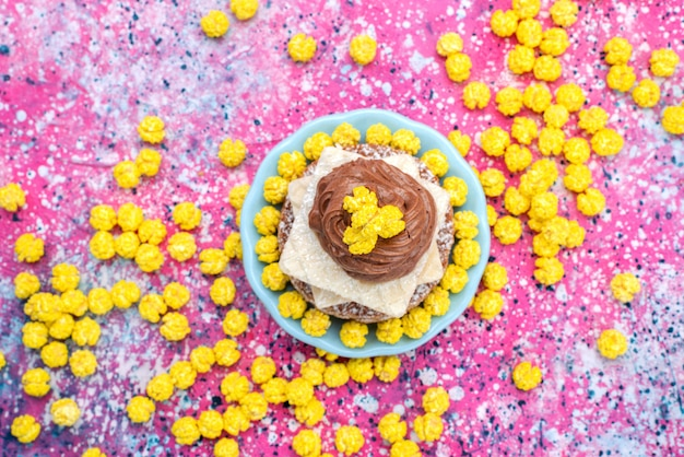 Top view delicious sweet cake with cream inside plate with yellow candies on the colorful background cake biscuit sugar dough bake color