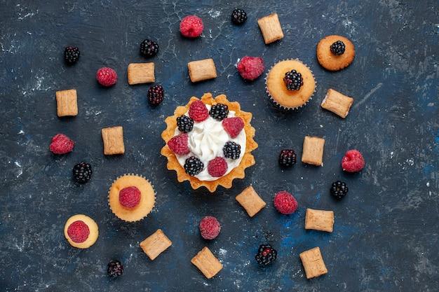 Vista dall'alto di una deliziosa torta dolce con biscotti di frutti di bosco diversi e crema gustosa su torta di colore grigio scuro, bacca di frutta, torta al forno