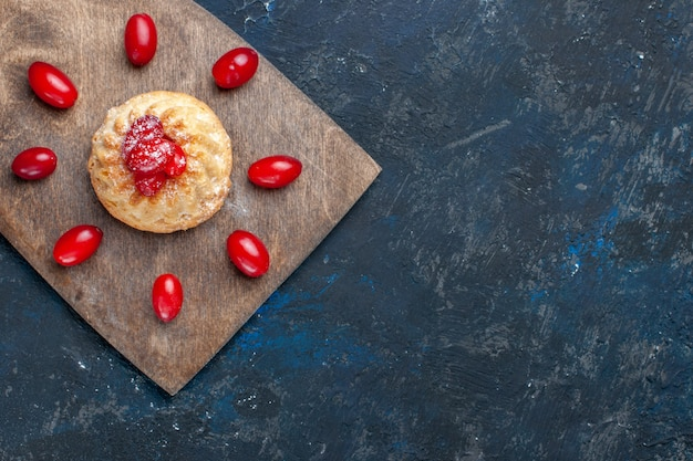 Top view of delicious sweet cake with red dogwoods on dark-grey desk, fruit berry color cake biscuit