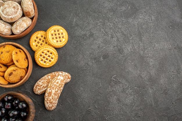 Vista dall'alto deliziose torte dolci con biscotti e olive sulla torta torta di superficie scura dolce