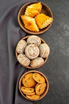 Вид сверху вкусные сладкие пирожные с печеньем на темной поверхности сладкого пирога с пирогом