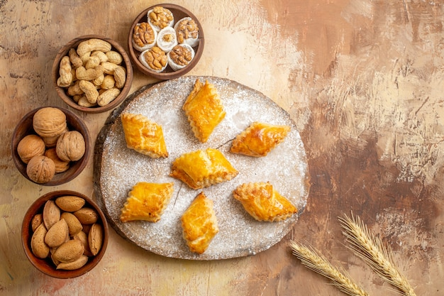 Top view delicious sweet cakes with different nuts on wooden desk pie biscuit nut