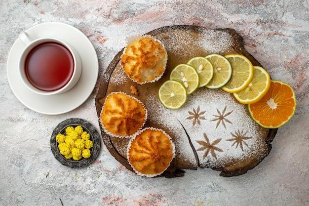 Vista dall'alto deliziose torte dolci con fette di limone e tazza di tè su superficie bianca