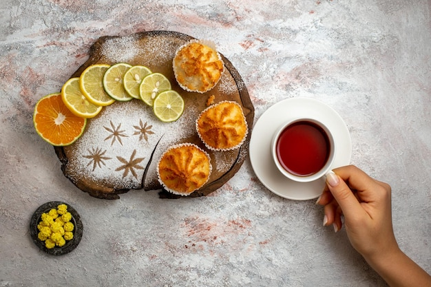 Top view delicious sweet cakes with lemon slices and cup of tea on white surface