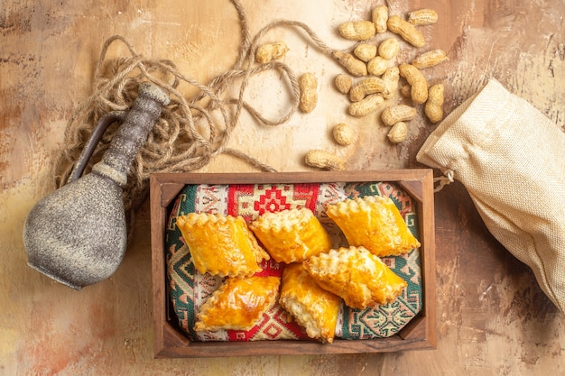 Top view of delicious sweet cakes with peanuts on wooden surface