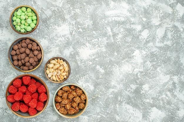 Вид сверху вкусные сладкие конфеты, разные сладости на белом пространстве