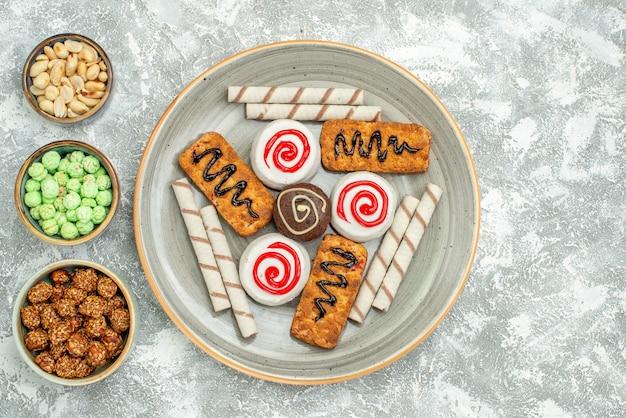 Vista dall'alto deliziosi biscotti dolci con torte e caramelle su uno spazio bianco