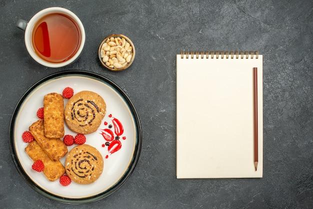 Vista dall'alto deliziosi biscotti dolci con una tazza di tè su uno spazio grigio