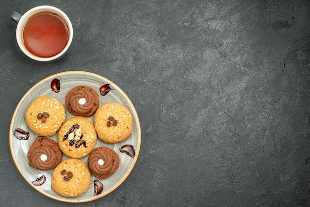 Vista dall'alto deliziosi biscotti dolci deliziosi dolci per il tè sullo spazio grigio