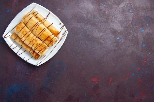 Vista dall'alto deliziosi pasticcini dolci all'interno della piastra sullo spazio viola scuro