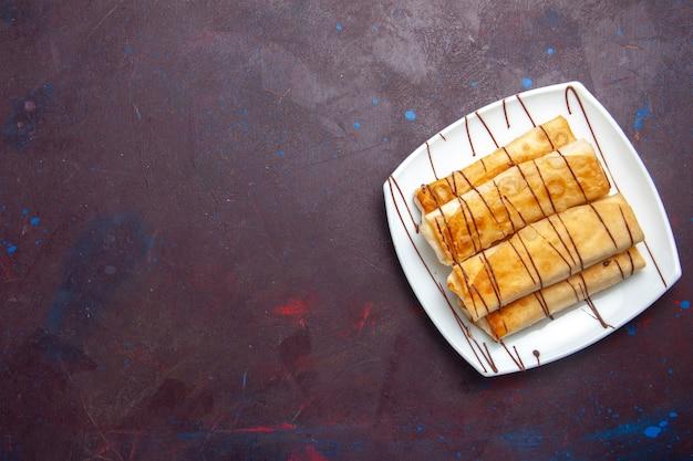 Vista dall'alto deliziosi pasticcini dolci all'interno del piatto nello spazio buio