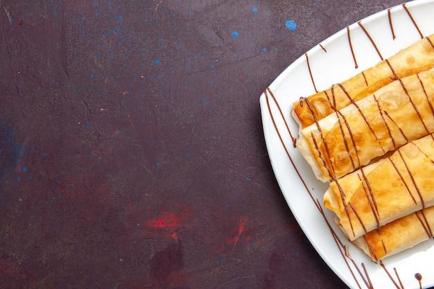 Вид сверху вкусной сладкой выпечки внутри тарелки на темном пространстве
