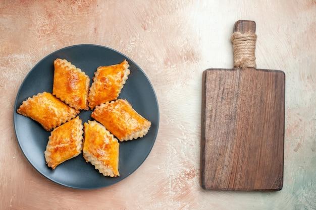 白いテーブルの上のプレート内のおいしい甘いペストリーの上面図ペストリー甘いケーキパイ