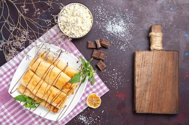 暗い空間にチョコレートとカッテージチーズを添えたトップビューのおいしい甘いペストリー