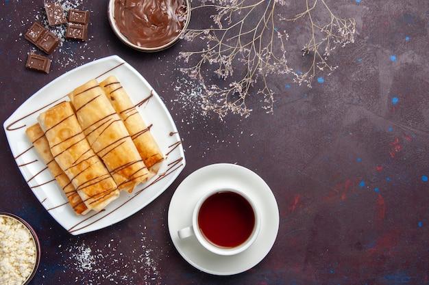 Вид сверху вкусной сладкой выпечки с шоколадом и чашкой чая на темно-фиолетовом пространстве