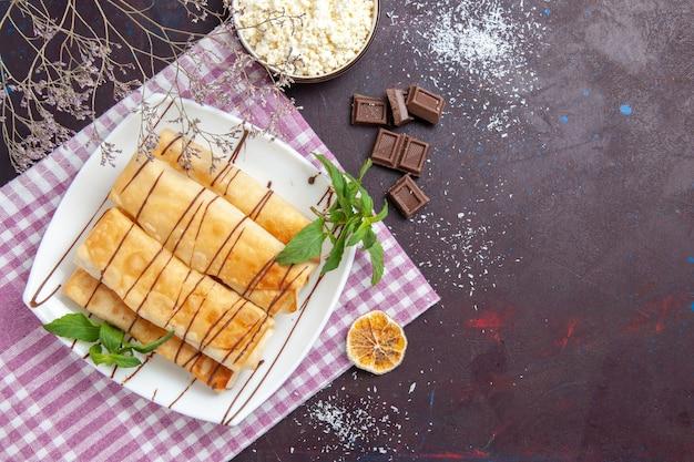 Vista dall'alto deliziosi pasticcini dolci con barrette di cioccolato sullo spazio buio